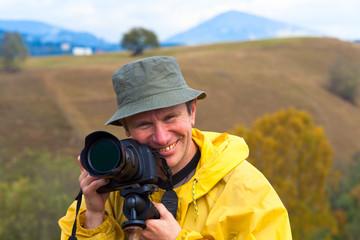 Happy photographer on autumn mountain background