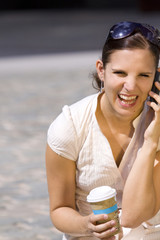Female with coffee laughing on the phone