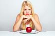 frustrierte frau isst einen roten apfel mit besteck