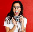 Excited young woman shouting holding a camera