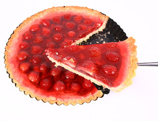 Strawberry Tart in a tart pan with a slice of it cut out