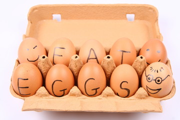 Eggs with an inscription EAT EGGS and faces in an egg carton
