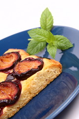 Piece of Plum Pie on a blue plate decorated with a mint twig