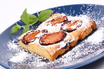Plum Pie covered with powder sugar on a plate with a mint twig