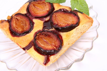 Piece of Plum Pie on a plate decorated with a mint twig