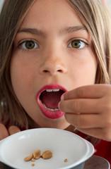 fillette mangeant des cacahuètes