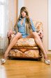 Pretty young woman sits on the armchair.