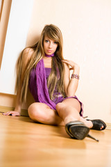 The sensual woman in a violet dress sits on the wooden floor.