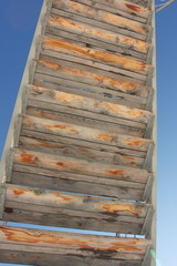 Wooden steps of the stairs against a blue sky
