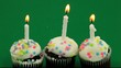 Three birthday cupcakes with candles burning