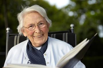 Nette alte Dame mit Buch lächelnd