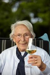 Nette alte Dame mit Wein lächelnd