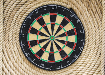 Dartboard hanging on old rope wall