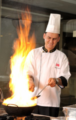 Professional cook preparing food on flame.