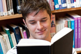 Portrait of a smiling male student reading a book sitting on the