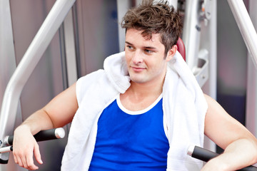 Cute relaxed man with a towel using a bench press