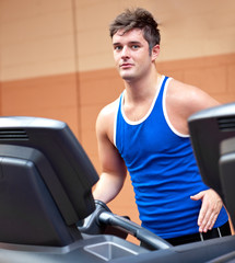 Good-looking man exercising on a running machine