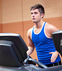 Concentrated athletic man training on a running machine
