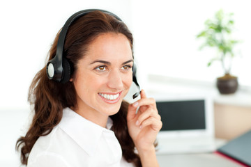 Smiling woman with headset working in a call center