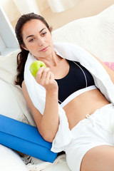 Tired woman eating an apple on the sofa after working out in the