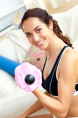 Smiling athletic woman holding a dumbbell in her living-room