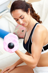 Young athletic woman holding a dumbbell in her living-room