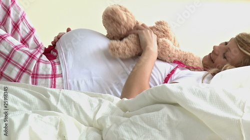 cute future mom lying and playing with a teddy-bear