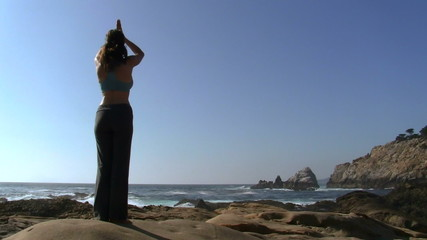 Woman practices yoga by the ocean - HD