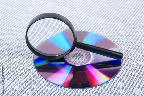 magnifying glass with DVD on binary code