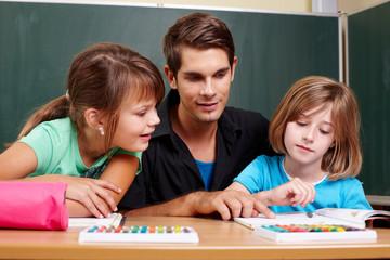 Lehrer gibt Hilfestellung