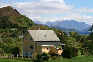 Alleinstehendes Holzhaus vor einer sommerlichen Landschaft