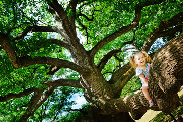 Happy cute toddler girl sitting on branch huge tree