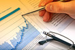Business man's hand showing diagram on financial report with pen