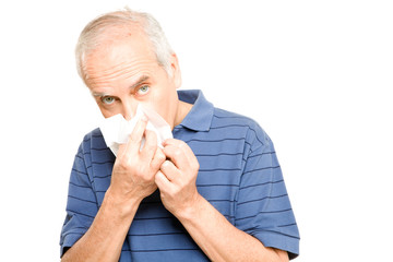 Senior man blowing nose