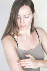 Woman applying lotion on her arm