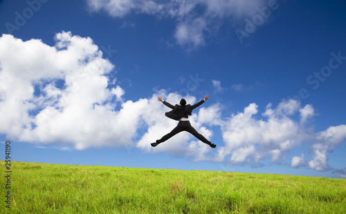 Businessman jumping on a green meadow