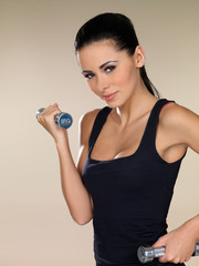 Young beautiful woman during fitness time with dumbbells