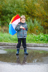 Cute boy outdoors at rainy day