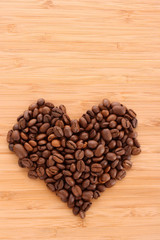 Coffee beans in heart shape on brown background