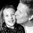 proud daddy kissing daughter in black and white