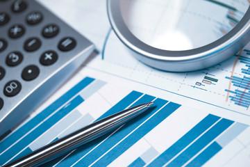 Profit bar chart, calculator and pen.