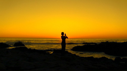 Woman in prayer pose at sunset - HD