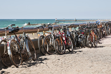 Many bikes along the beach during a beautiful day