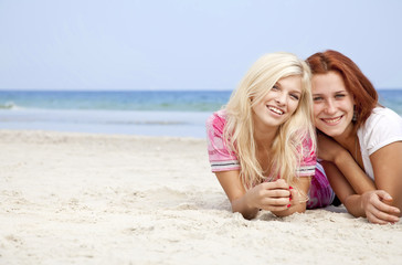 Two girl friends lying down at the beach.