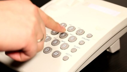 Business man pushing buttons with numbers on telephone