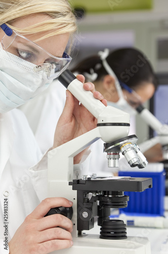 Female Scientific Research Team & Microscopes in a Laboratory