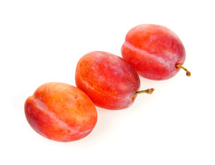 couple of plums in closeup over white background