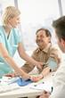 Smiling nurse measuring blood pressure of patient
