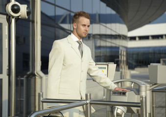 young caucasian businessman standing at the security gate