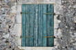 Stone wall and blue window shutter.